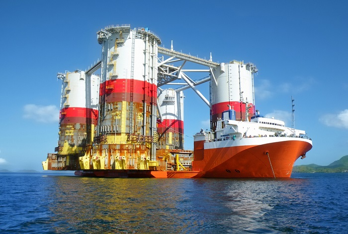 A heavy lift cargo ship transports an oil rig.