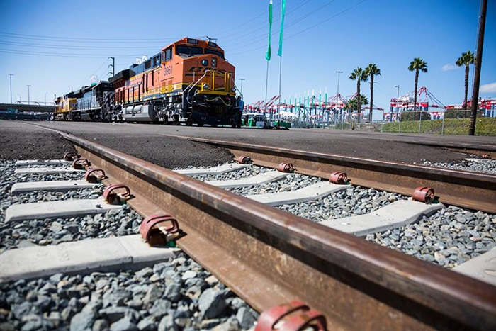 A BNSF train travels near the Port of Long Beach.