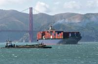 A container ship passes under the Golden Gate Bridge.