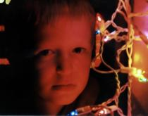 Serious-looking boy with Christmas lights