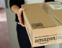 A delivery person presents an Amazon package
