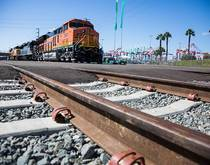 A BNSF train travels near the Port of Long Beach.
