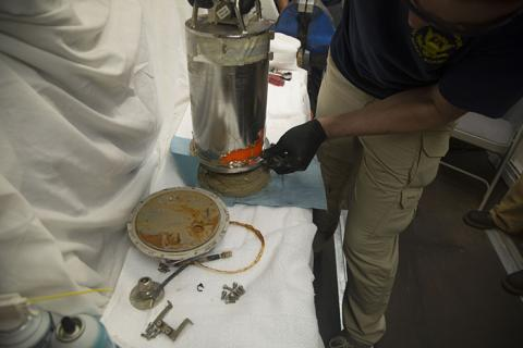 National Transportation Safety Board engineer Douglas Mansel begins the process of disassembling El Faro's voyage data recorder capsule Aug. 9, 2016 aboard the USNS Apache.